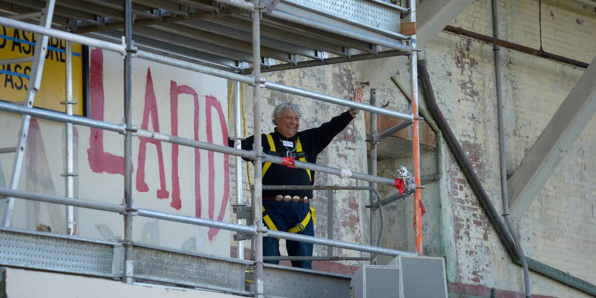 Alcatraz occupier waves after painting political slogan during 50th anniversary celebration