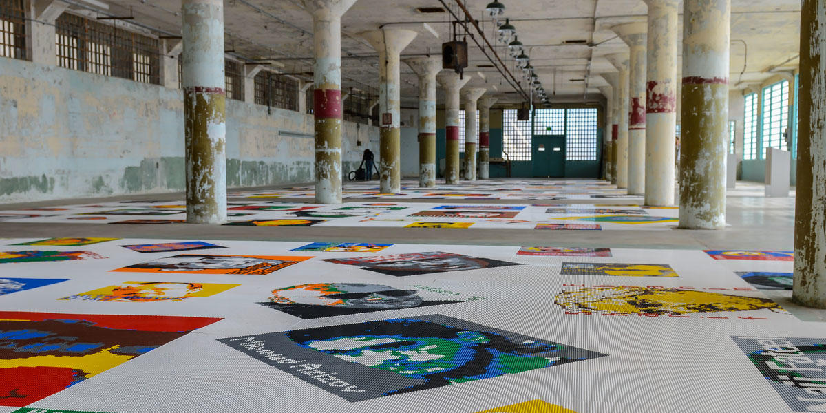 Lego brick pieces are arranged to create portraits along a floor inside a large concrete room with columns