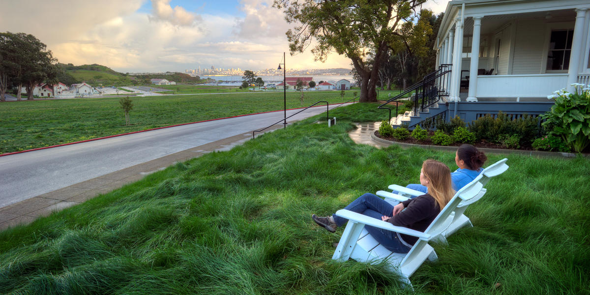 Two people sit in chairs and look out over a grassy field at the San Francisco skyline