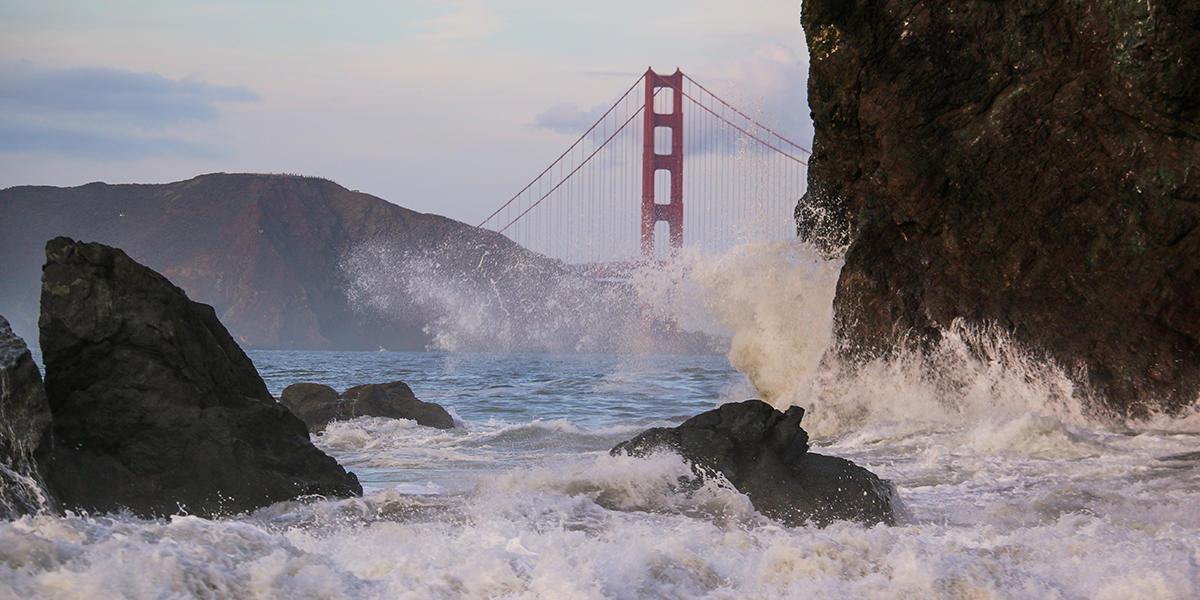 Waves crash before the Golden Gate Bridge