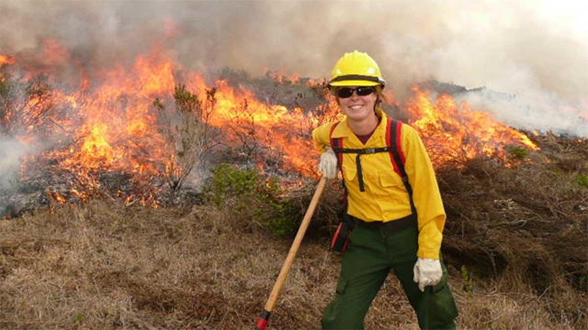 Alison Forrestel poses next to a grassland fire.