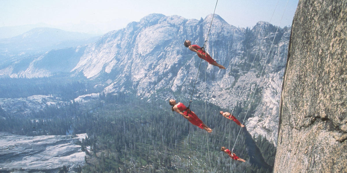 four people suspended from safety harnesses propel themselves away from the granite face of rock wall