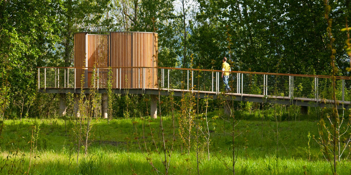 A person walks up a ramp toward an elliptical wooden structure
