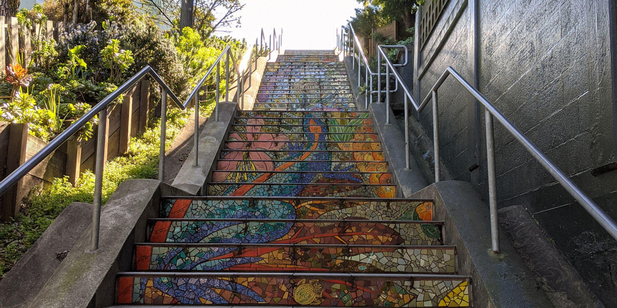 outdoor stairs adorned with colorful tiles are surrounded by plants and trees