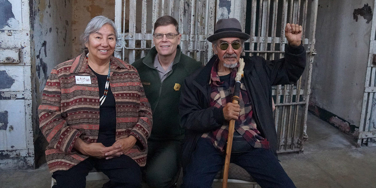 Three people sit smiling for the camera in the Alcatraz Cellhouse