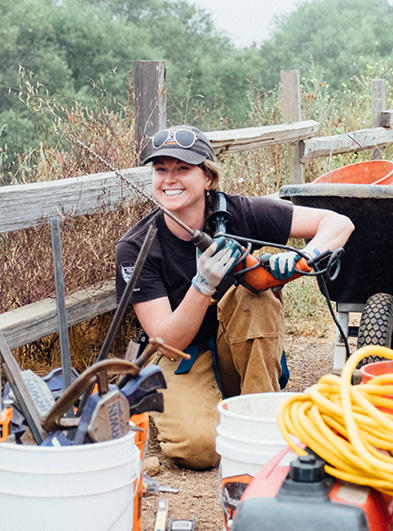 Katie Teschler gets ready to drill in some railings for fencing at Tennessee Valley during a drop-in program. (Parks Conservancy)