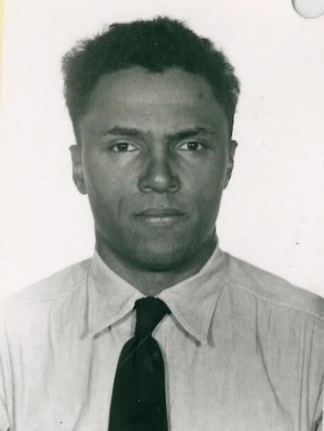 A black and white photograph of a Black man (Robert Lipscomb) in a white button-down shirt and a black tie. Presumably an intake photo for a federal prison.