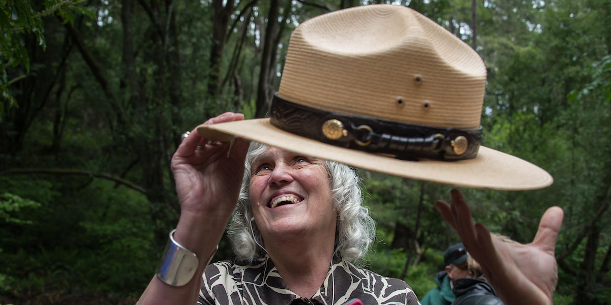 A visually impaired woman feels the NPS ranger hat.