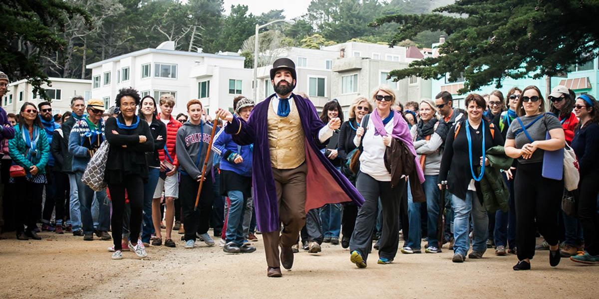 Person in costume leading a crowd of audience members through a park