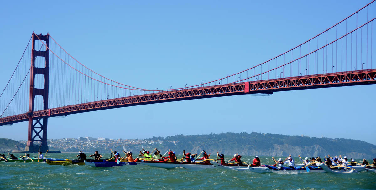 Outrigger canoes paddle under the Golden Gate Bridge.