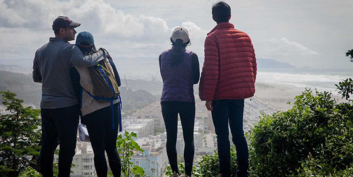 Four people stand on edge of Sutro Heights Parks looking out towards Ocean Beach and Golden Gate Park