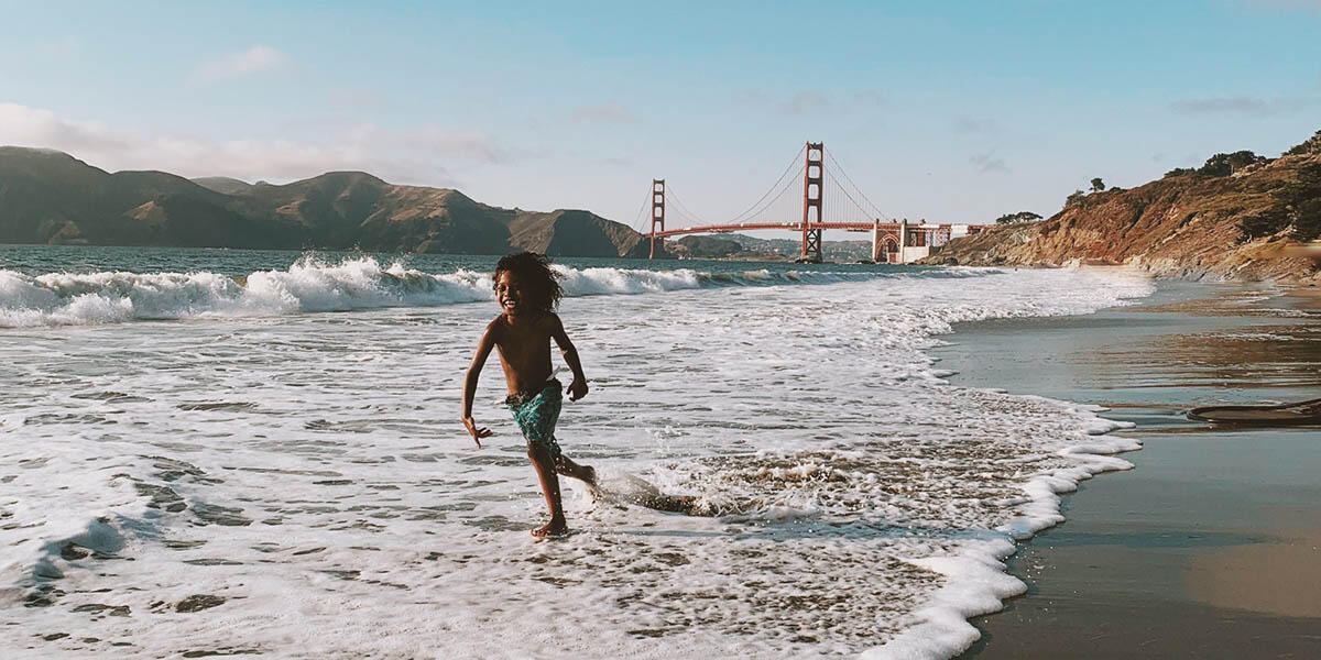 Child plays in the waves with Golden Gate Bridge in background.