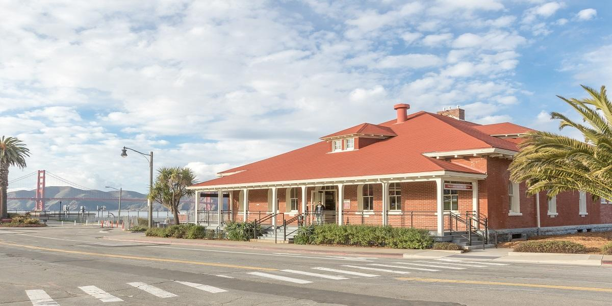 Image of the front of the Presidio Visitor Center with the Golden Gate Bridge in the backgrounr
