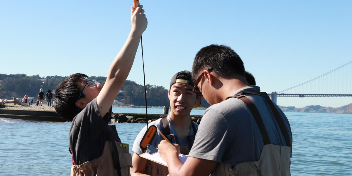 A small group of teenagers uses monitoring tools in the waters off of Crissy Beach