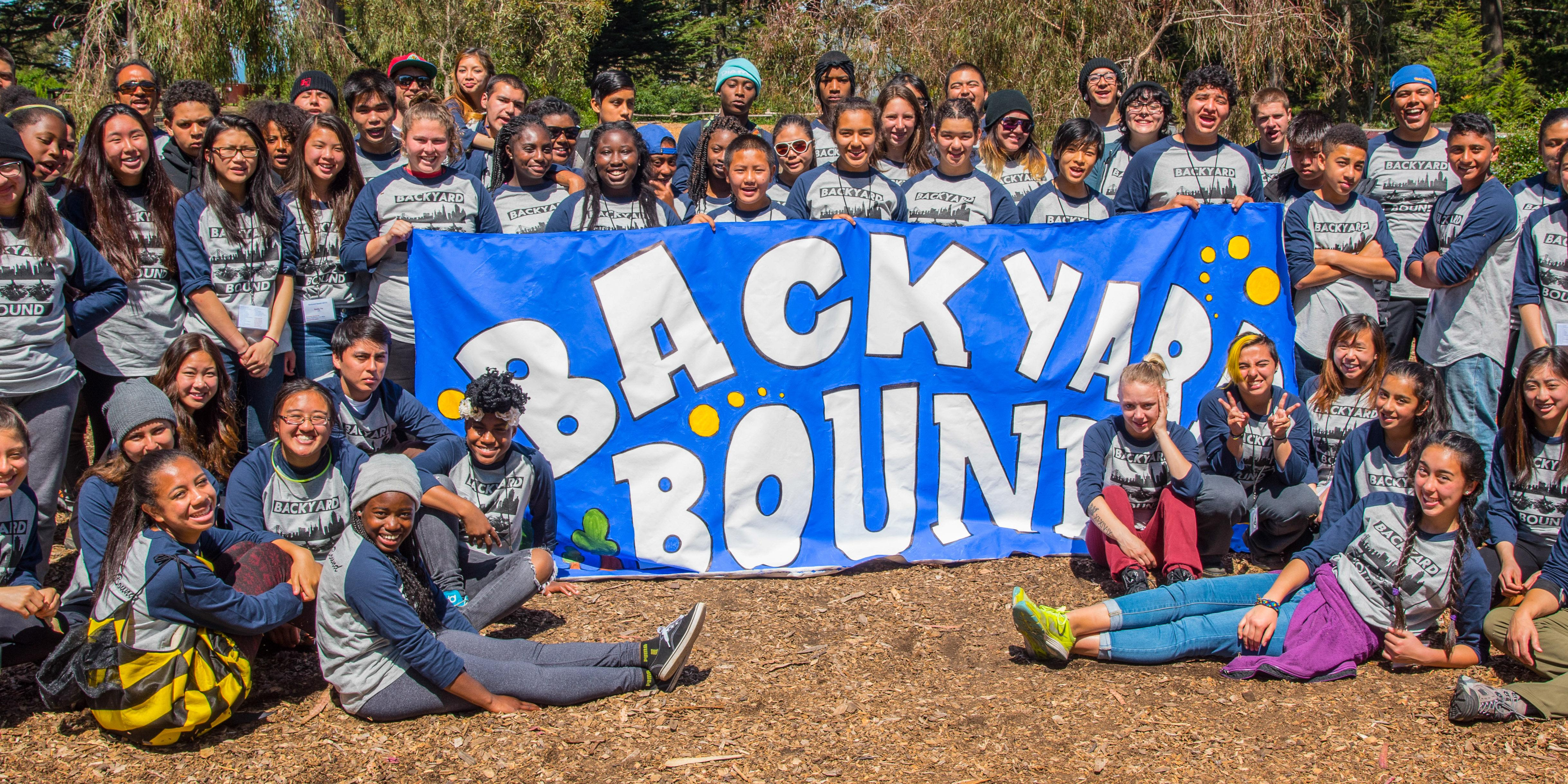A large group of youth and youth workers gather around a banner reading Backyard Bound