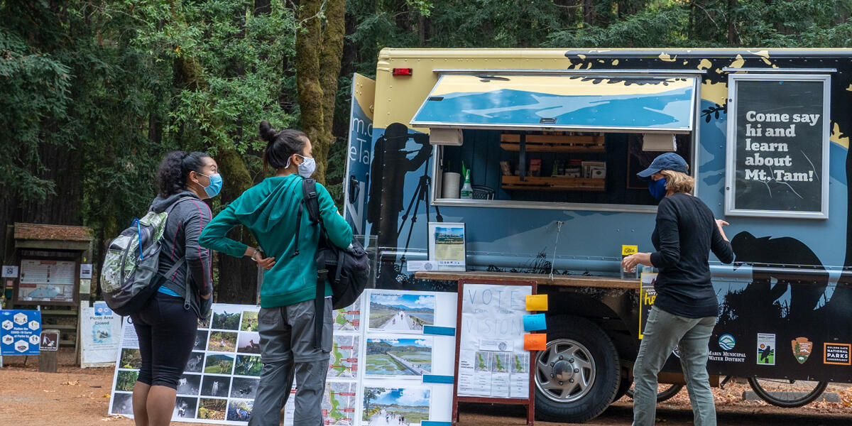 A masked staff member of ONE TAM greets park visitors with the Roving Ranger at Mount Tamalpais.