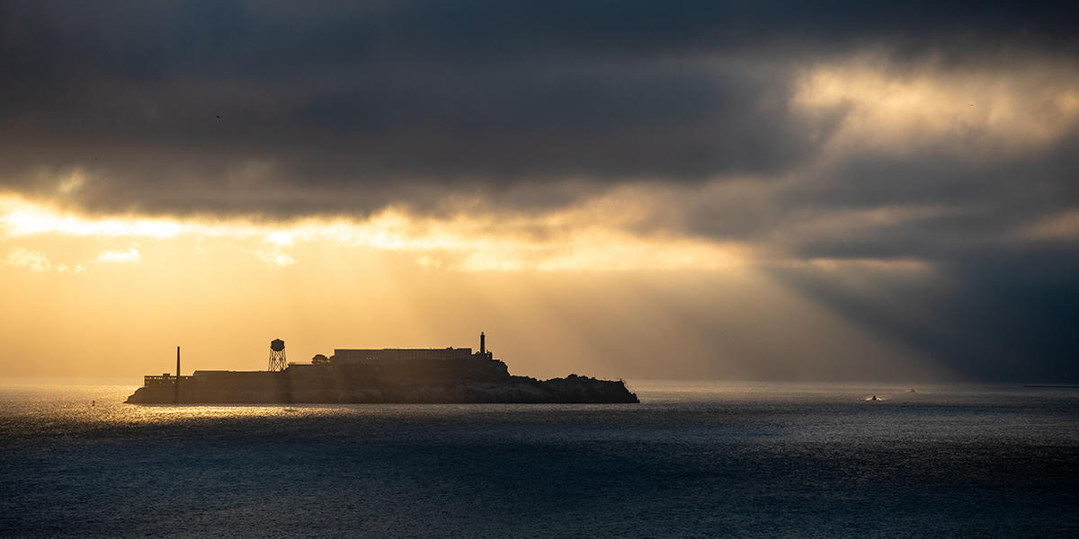 Sunlight breaks through gloomy fog over Alcatraz Island