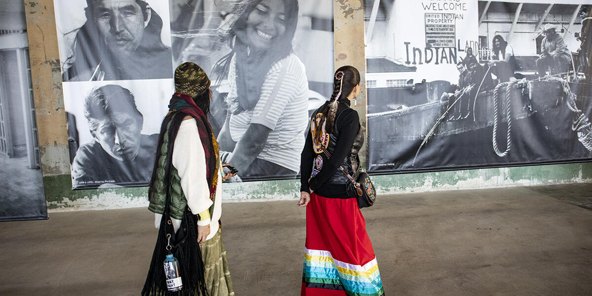 women walk past black and white photos