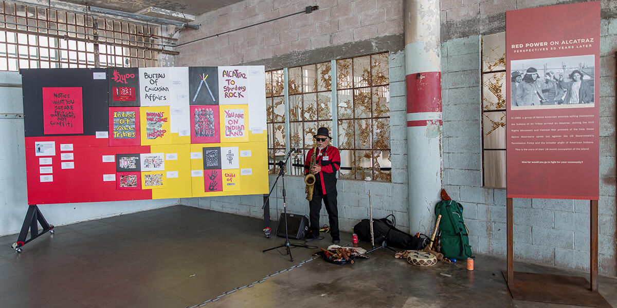 Man playing saxophone surrounded by slogans about Red Power on Alcatraz