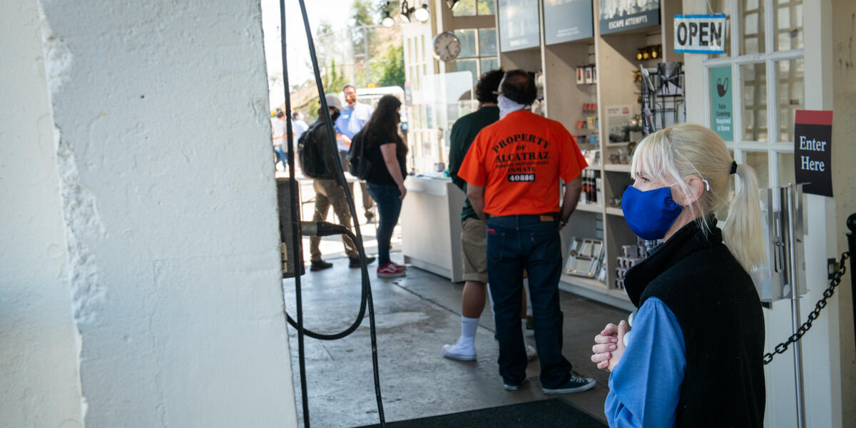 Masked workers prepare to assist visitors for the re-opened tours of Alcatraz Island.