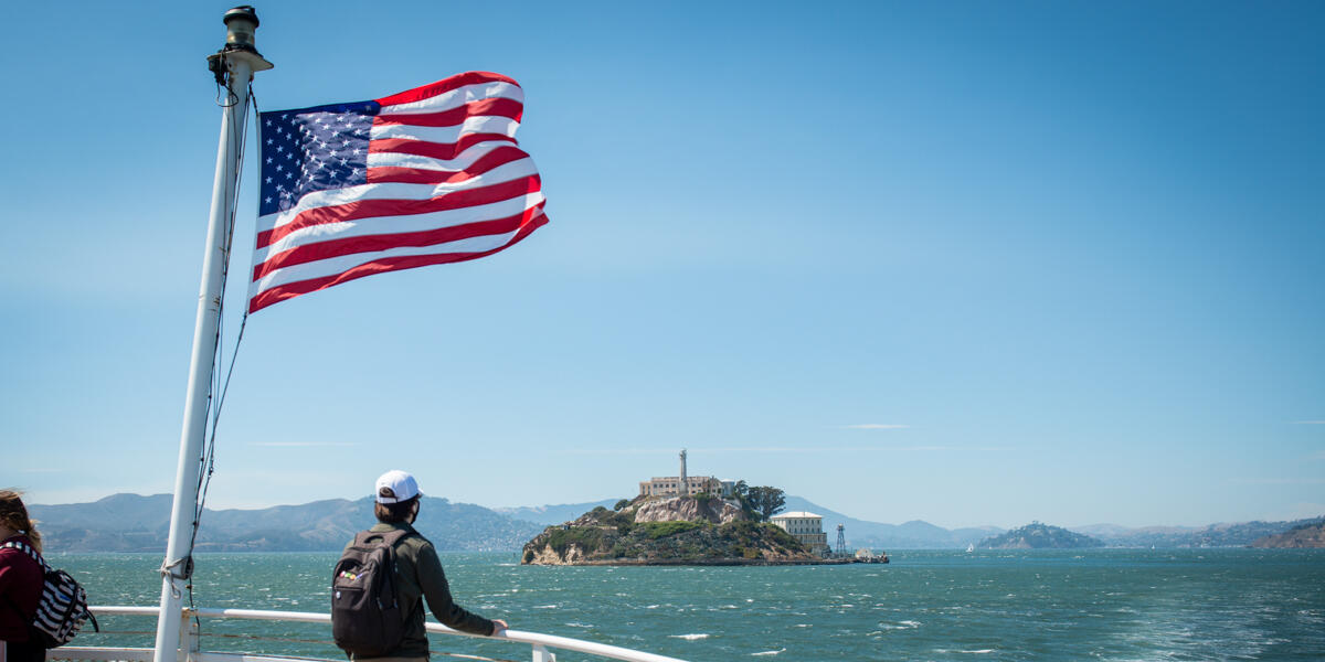 A park visitor looks toward Alcatraz Island from the ferry. An American flag waves in the breeze as they cruise over bay waters.