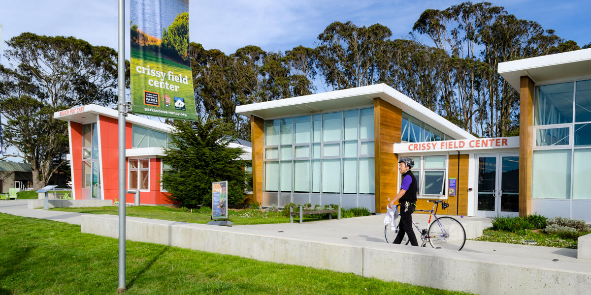 A park visitor at Crissy Field walks his bike by Crissy Field Center.