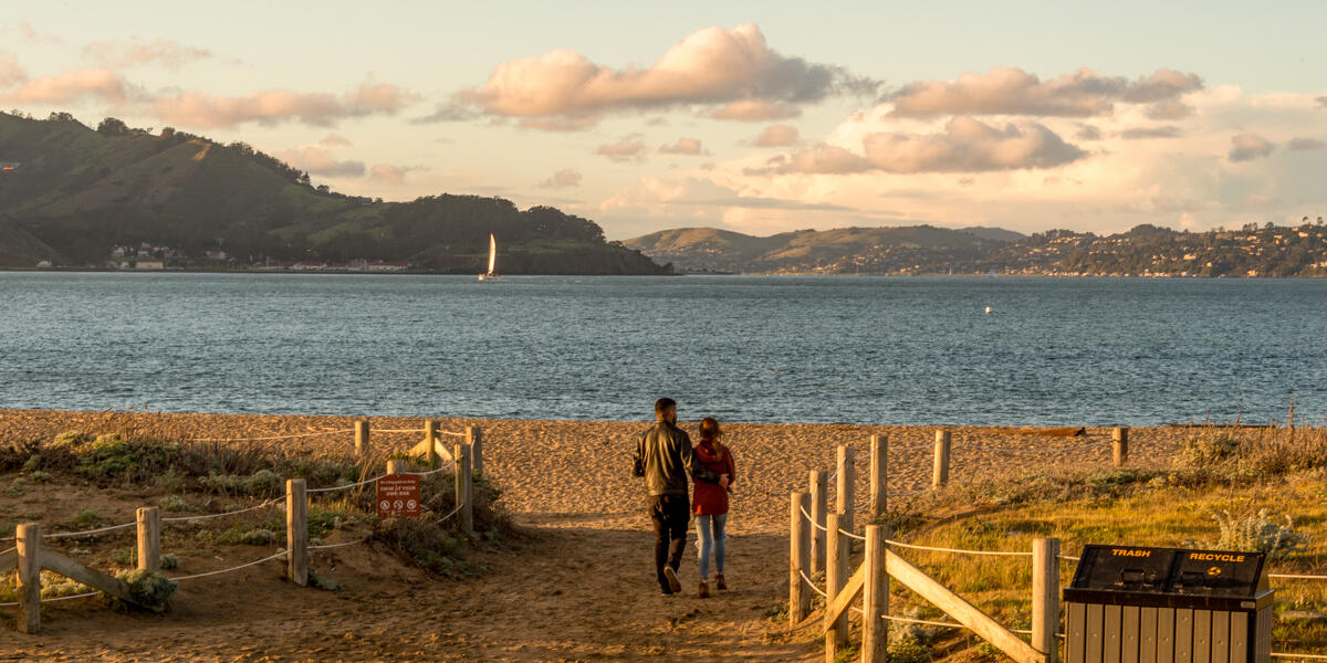 Visitors step out onto Crissy Field East Beach where the sunset casts warm light over the Golden Gate and San Francisco bay.