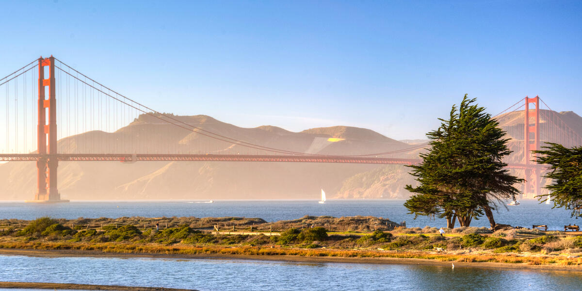 The Golden Gate Bridge as viewed from Crissy Field. The bay waters can be seen with sailboats about, as well as Crissy Marsh and the Marin Headlands.