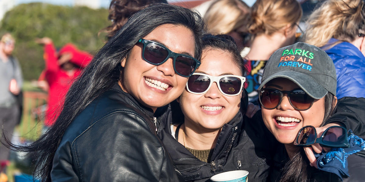 Three woman wearing sunglasses smile for photo.