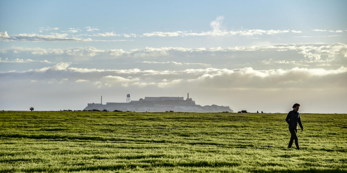 A view of Alcatraz from Crissy Field. A park visitor walks across the green grass under the blue sky.
