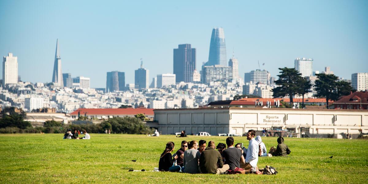 Park visitors enjoy a picnic sitting on the lawn at Crissy Field amongst the San Francisco city skyline on a sunny day.