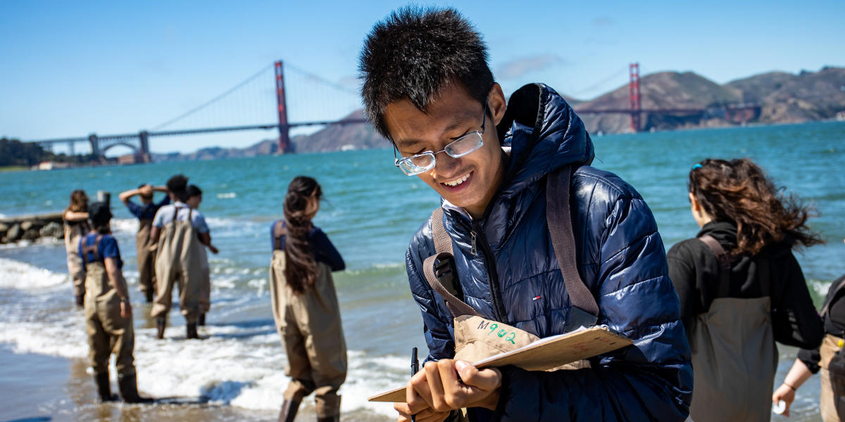 Youth participating in Project WISE are mentored by staff from the Crissy Field Center as they learn about water testing in the Marsh at Crissy Field.