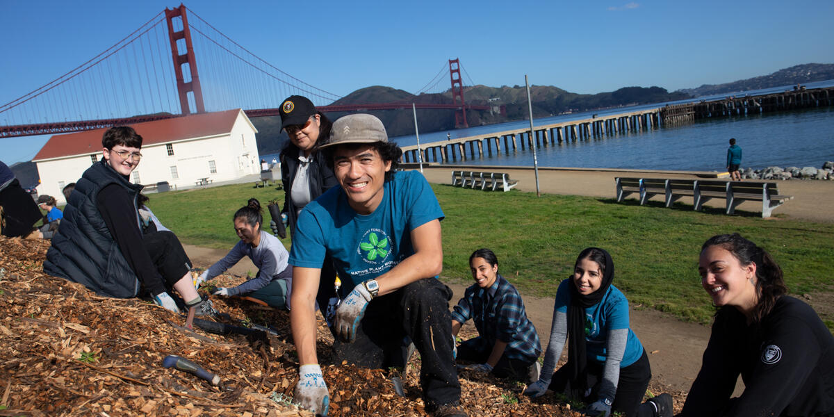 Interns smile for a photo while doing park stewardship work at Crissy Field.