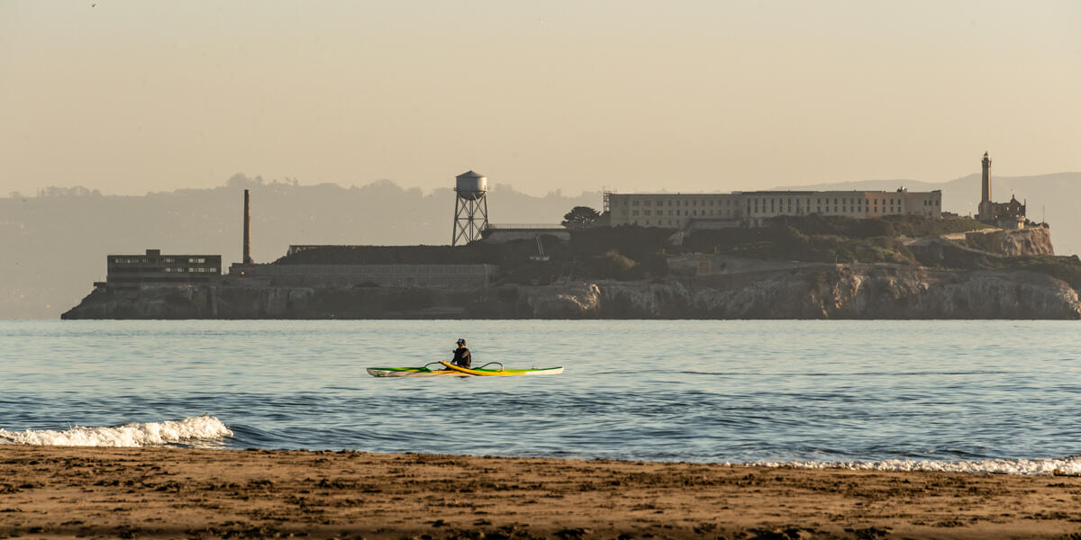 A Kayak paddles over the Golden Gate waters, viewed before Alcatraz Island from Crissy Field East Beach.