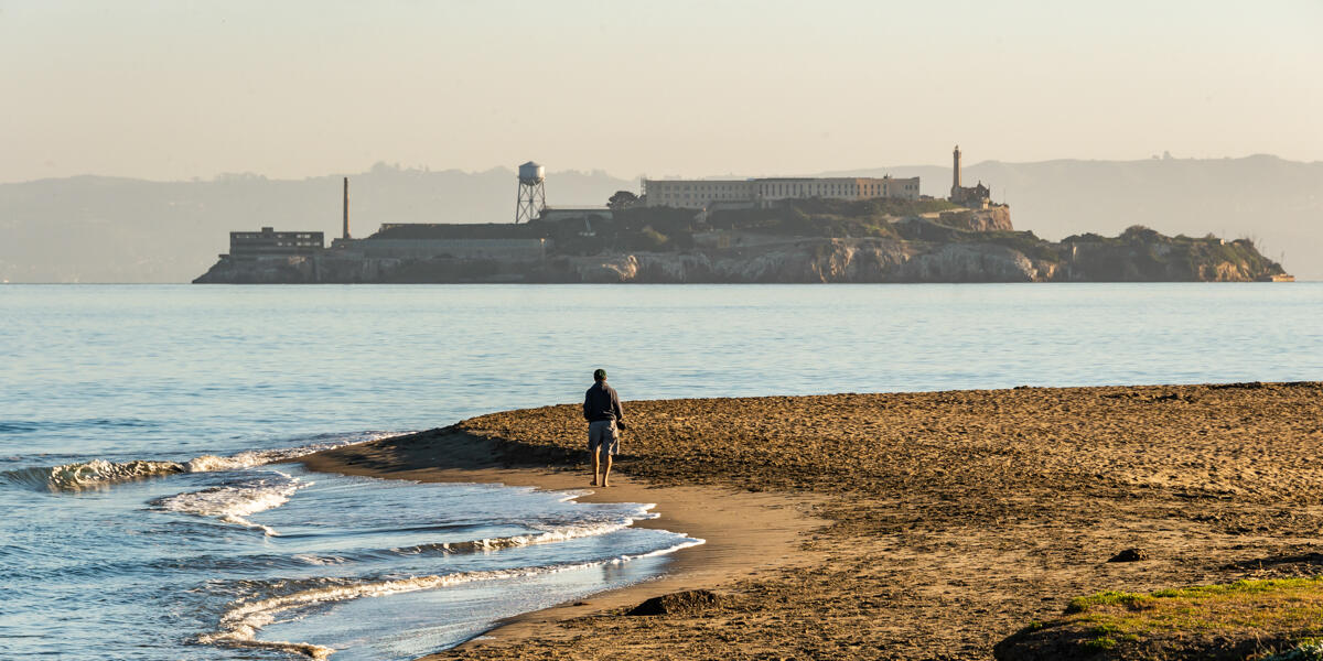 A park visitor walks along Crissy Field East Beach with a view of Alcatraz in the distance.