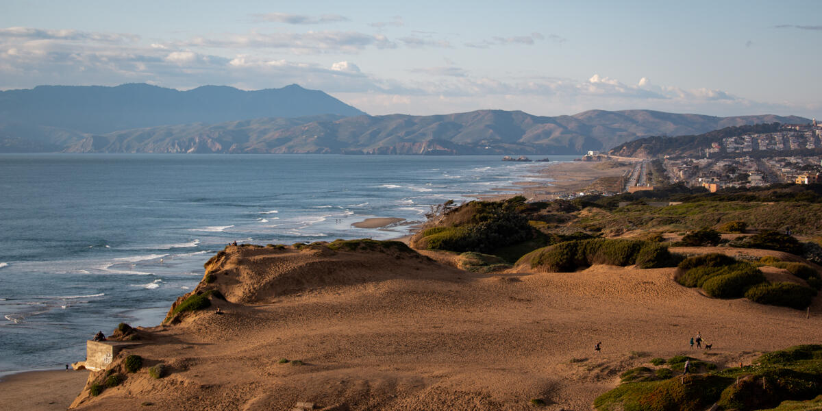 An aerial view of Fort Funston shows the ocean, beach, cliffsides, and looks on to the golden gate.