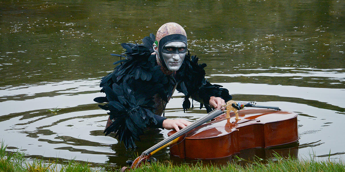Musician Andy Meyerson wears an elaborate costume with a cello floating in Sutro Baths.