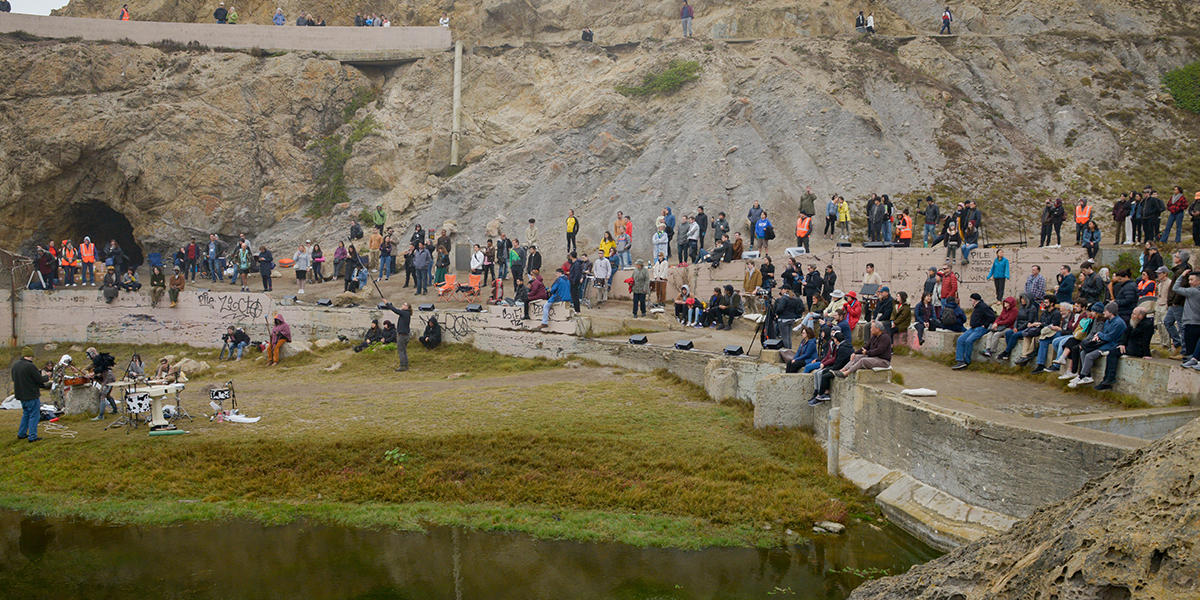 Musicians perform in front of crowd of onlookers at Sutro Baths.