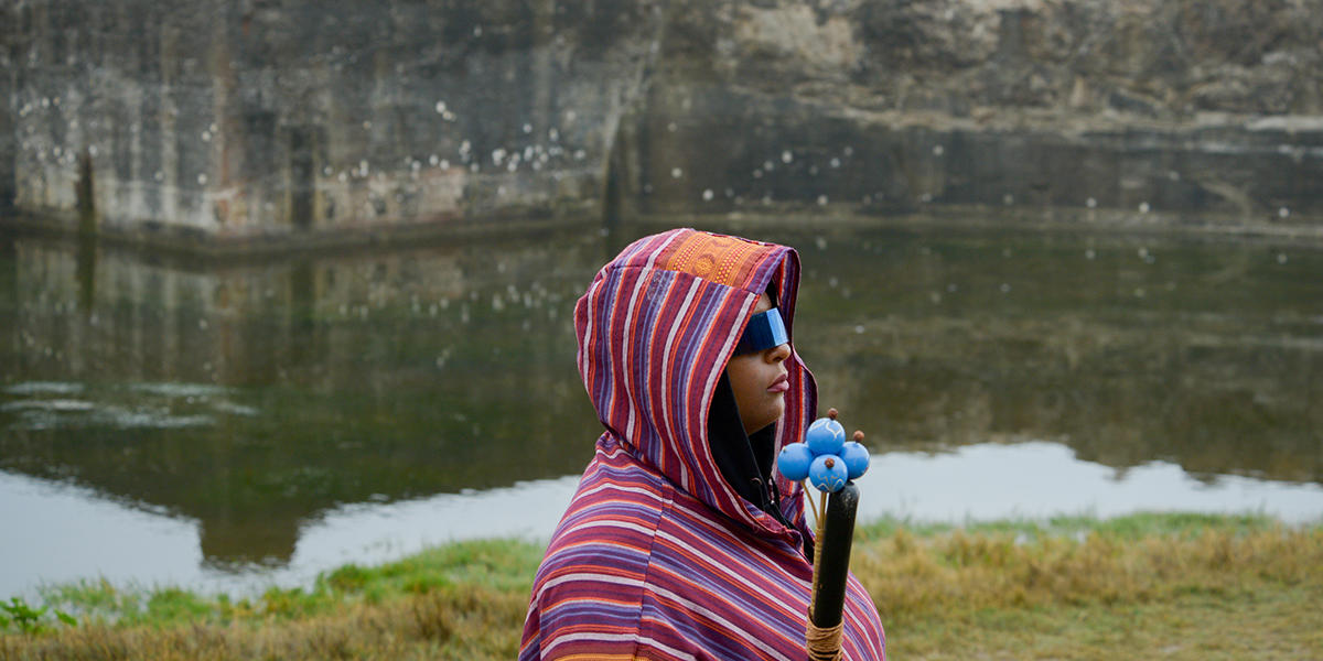 "Woman wearing hood stands by water at Sutro Baths during ""Tremble Staves."""