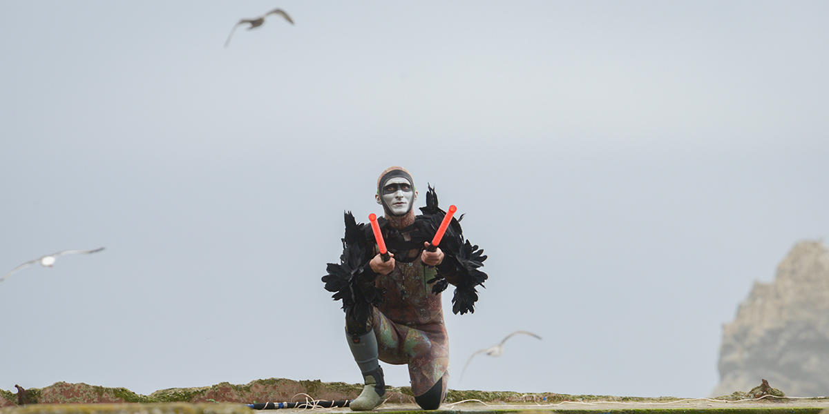 Musician Andy Meyerson wears an elaborate costume on ruins of Sutro Baths with birds flying in background.
