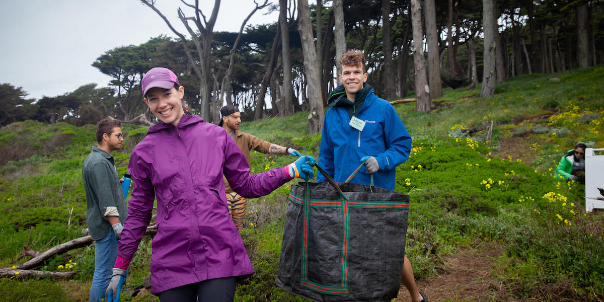 Two volunteers hold up bag full of weeds at Lands End in San Francisco