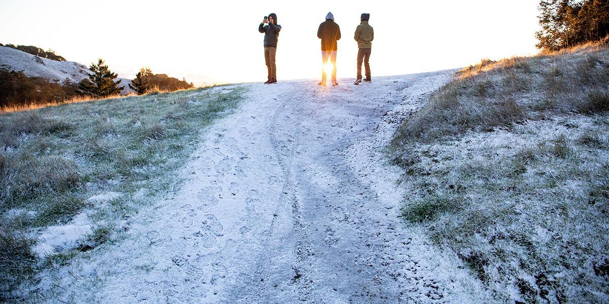 Teens look at snow on Mount Tam.