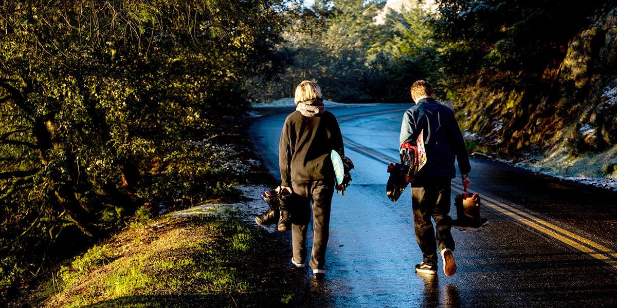 Teens with snowboards walk towards snow.