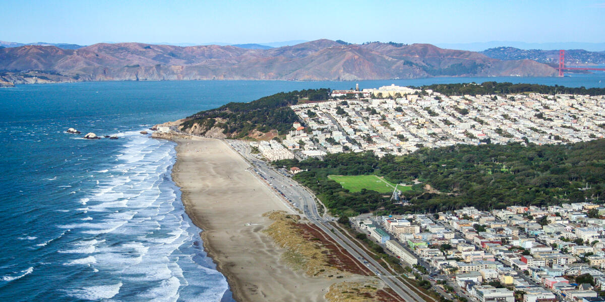 Aerial view of Ocean Beach showing waves lapping against the shore before San Francisco, along with the Golden Gate and Marin Headlands in the background.