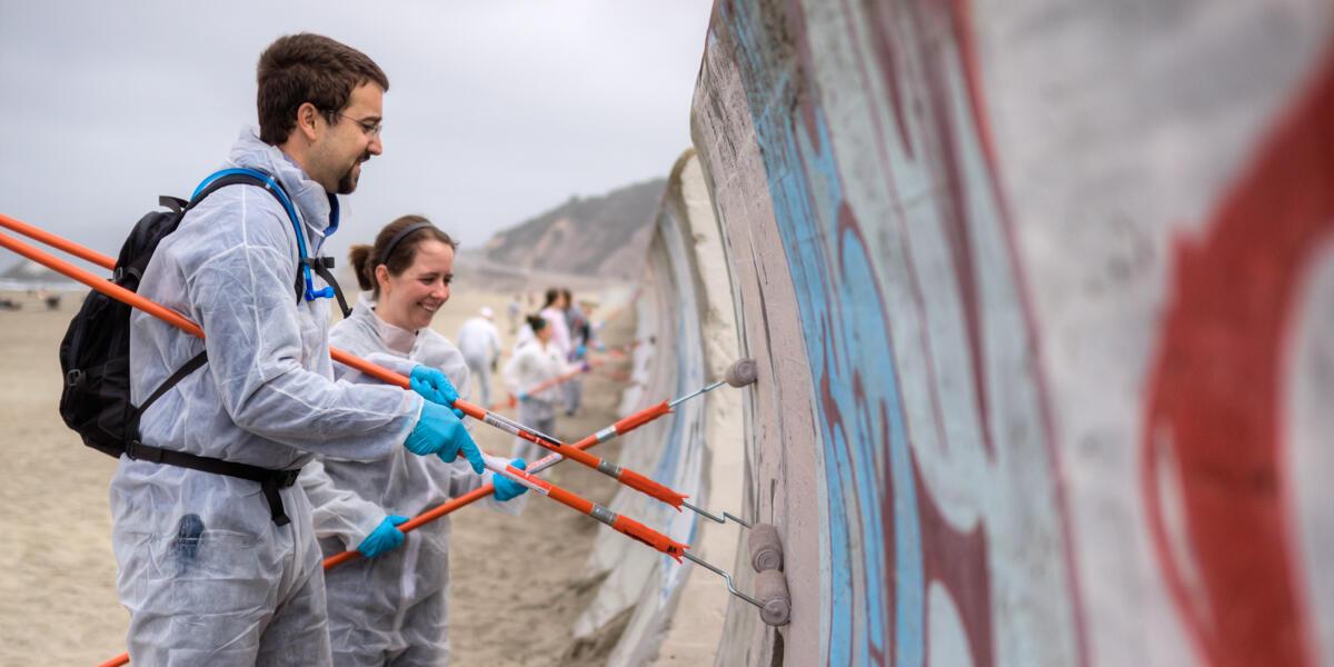 Park stewardship volunteers help to remove graffiti from the Ocean Beach seawall.