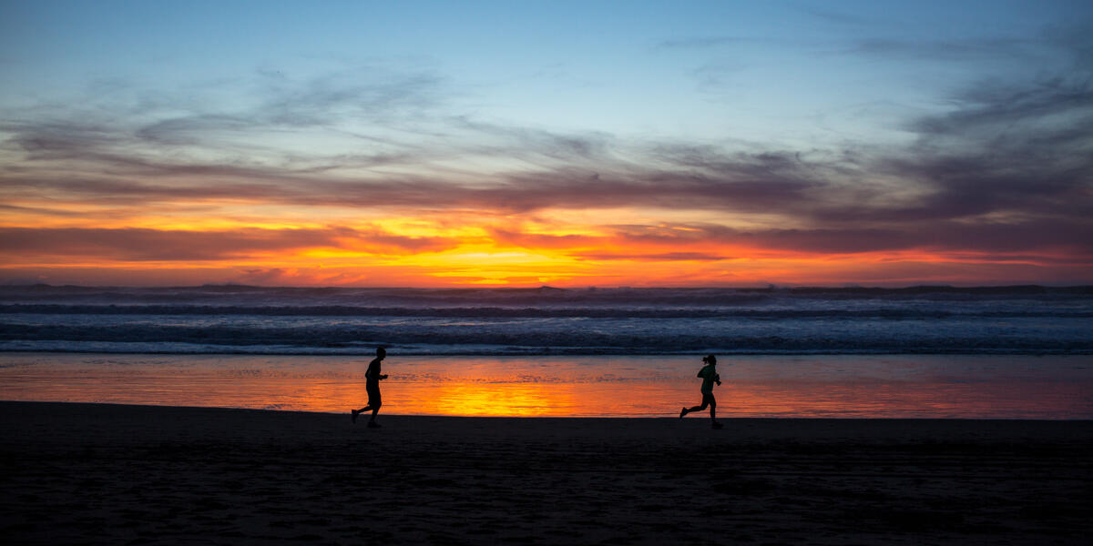Park visitors are going for a jog along the gorgeous red sunset and lapping waves at Ocean Beach.