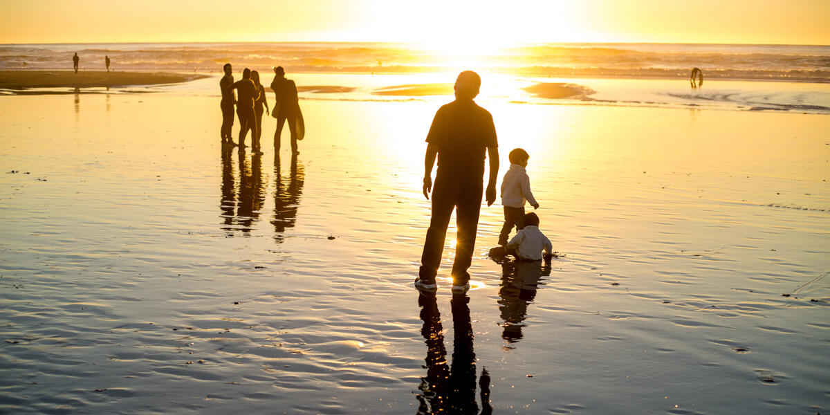 Visitors and families bask in a golden sunset where the water meets the sands of Ocean Beach.