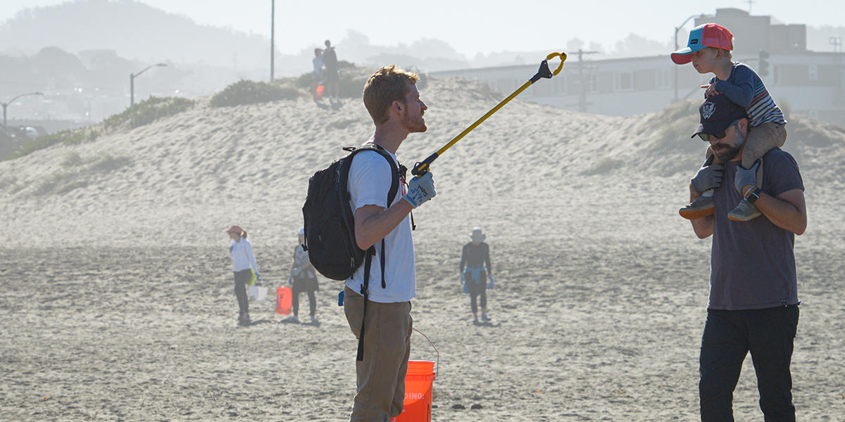 Adult shows trash to curious boy on his dad's shoulders on Ocean Beach in San Francisco.