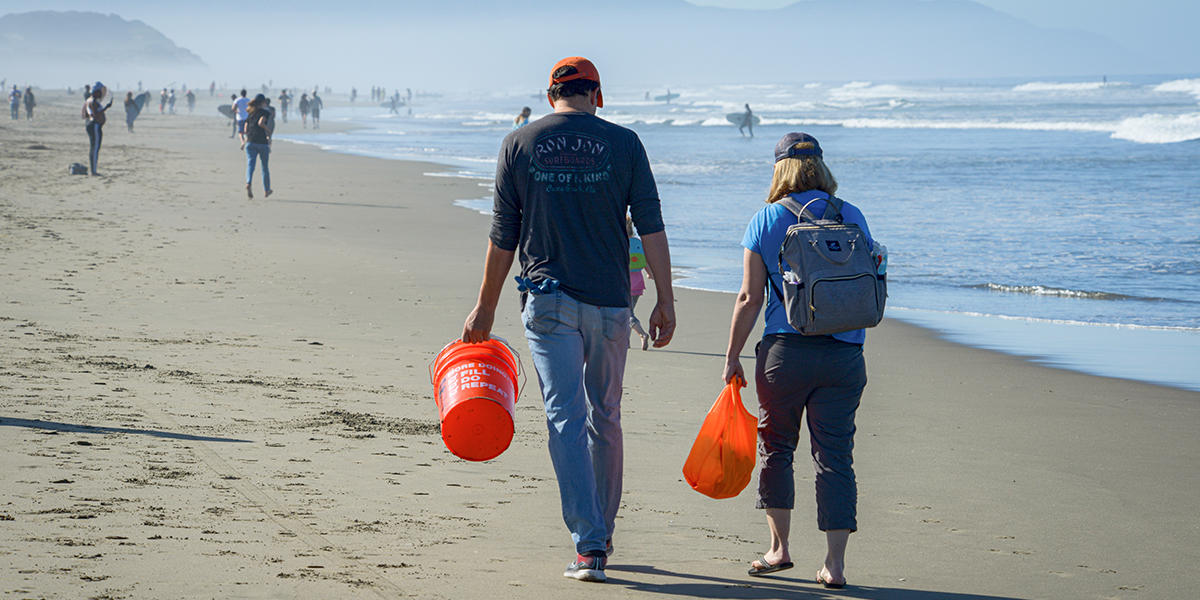 Bare-footed couple wants down Ocean Beach in San Francisco with buckets in hand.