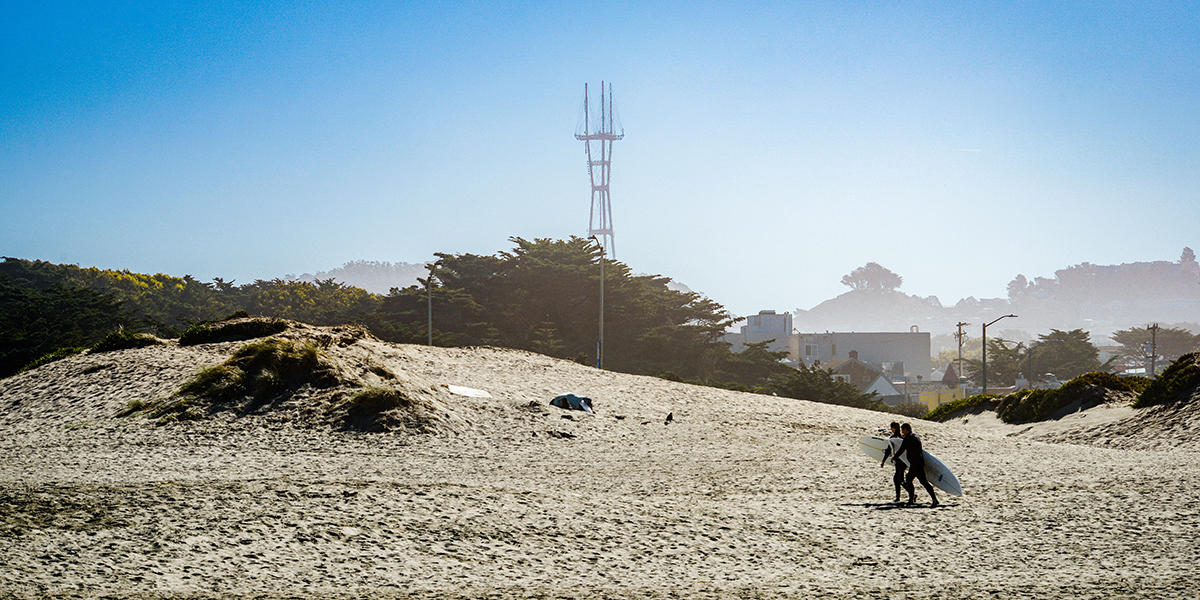 Surfers walk along Ocean Beach with Sutro Tower in the background